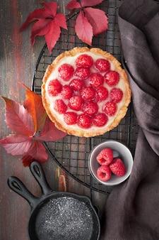 Czerwona malinowa tarta kruche z kremem waniliowym i szkliwionymi świeżymi malinami na stojaku chłodzącym na ciemnobrązowym