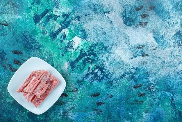 Czerwona marmolada w talerzu, na niebieskim stole.