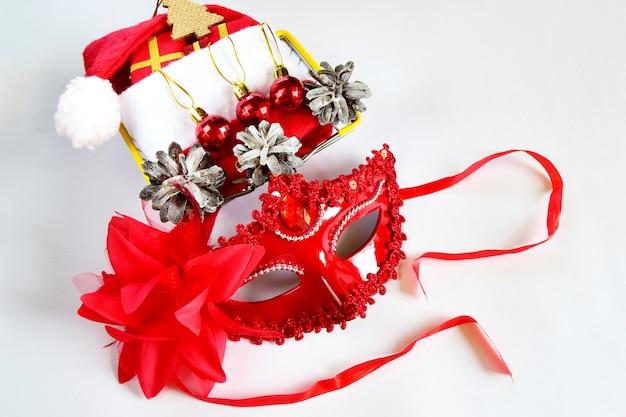 Czerwona maska karnawałowa, ozdoby świąteczne i czapka mikołaja w sylwestrowym wystroju.