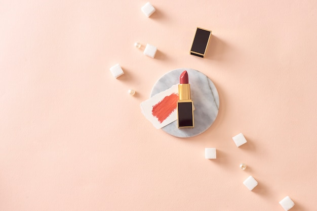 Czerwona matowa szminka na marmurowym cokole