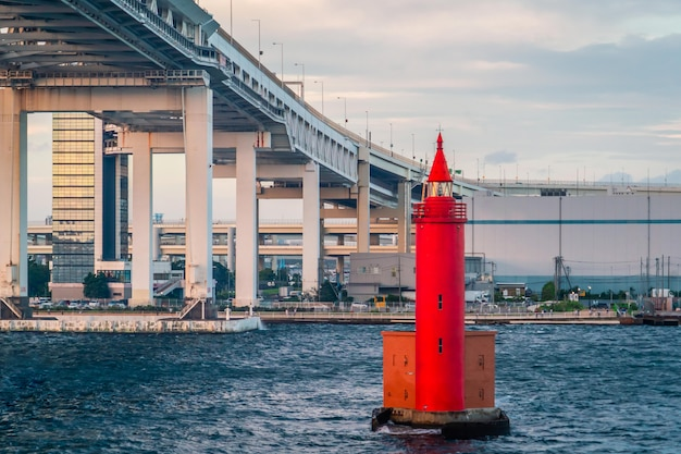 Czerwona metalowa latarnia morska pod mostem yokohama