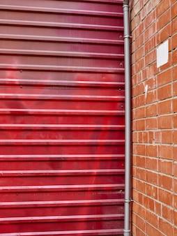 Czerwona metalu ściana z cegieł brama w miasta tle