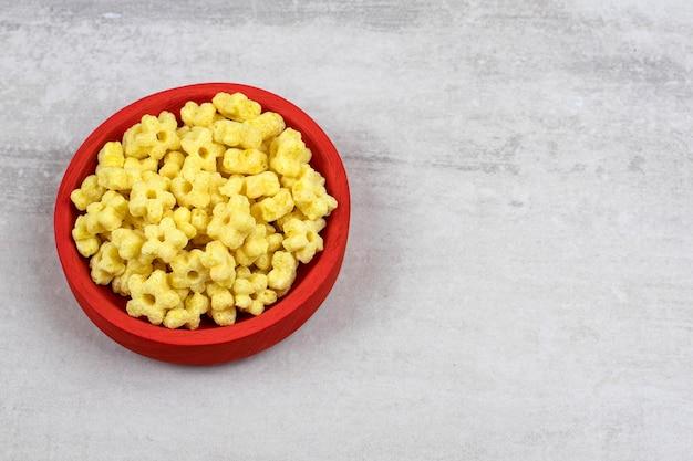 Czerwona miska pełna pysznych płatków kukurydzianych na kamiennym stole.