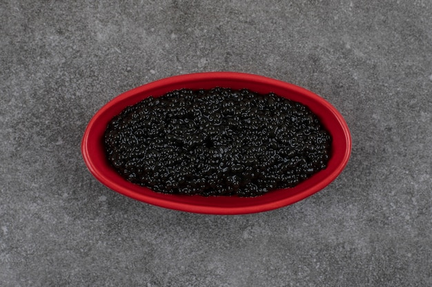 Czerwona miska pełna z czarnym kawiorem na szarym stole.