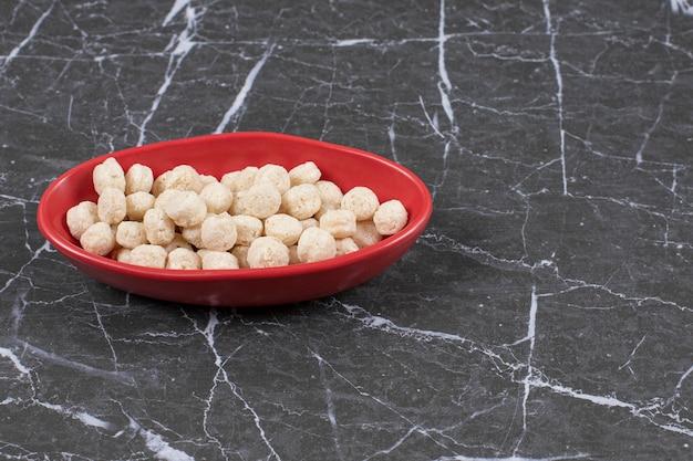 Czerwona miska słodkich kulek zbożowych na śniadanie. wysokiej jakości ilustracja