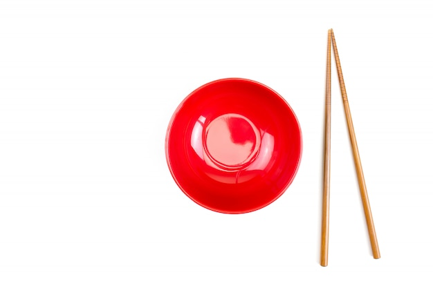 Czerwona miska z pałeczkami i na białym tle