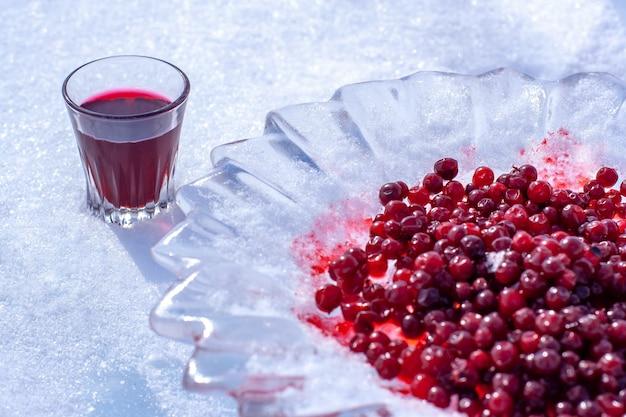Czerwona nalewka alkoholowa w małej szklance i żurawina w lodowym talerzu. alkohol w szklance stoi na śniegu. skoncentruj się na szkle. poziomy.