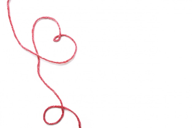 Czerwona nić i serce odizolowywający na bielu
