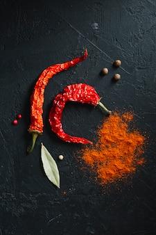 Czerwona ostra papryczka chilli i pikantny proszek leżały płasko