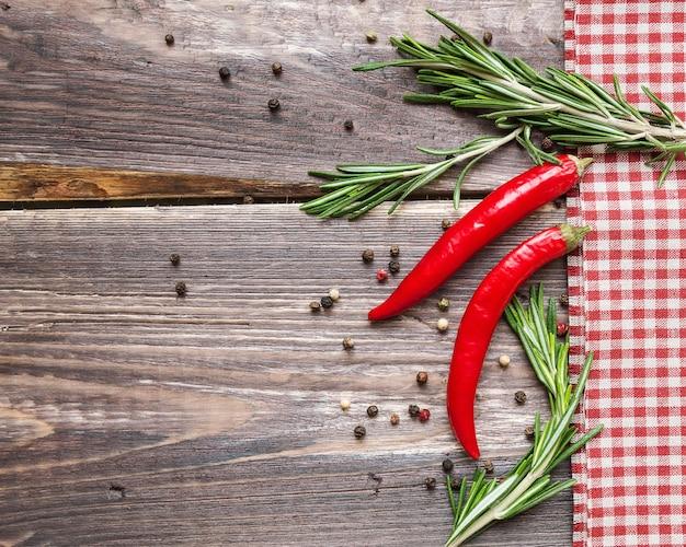 Czerwona ostra papryka i rozmaryn z serwetką w kratkę na rustykalnym drewnianym stole
