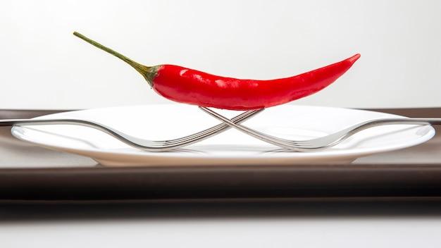 Czerwona ostra papryka z widelcem z bliska na talerzu