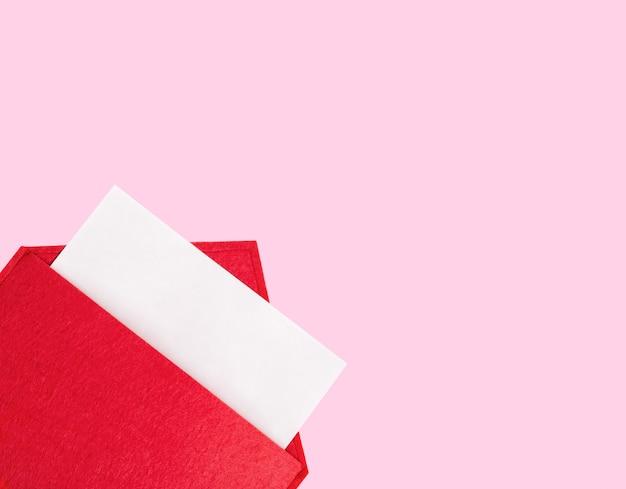 Czerwona otwarta koperta z kartką papieru makiety na różowym tle