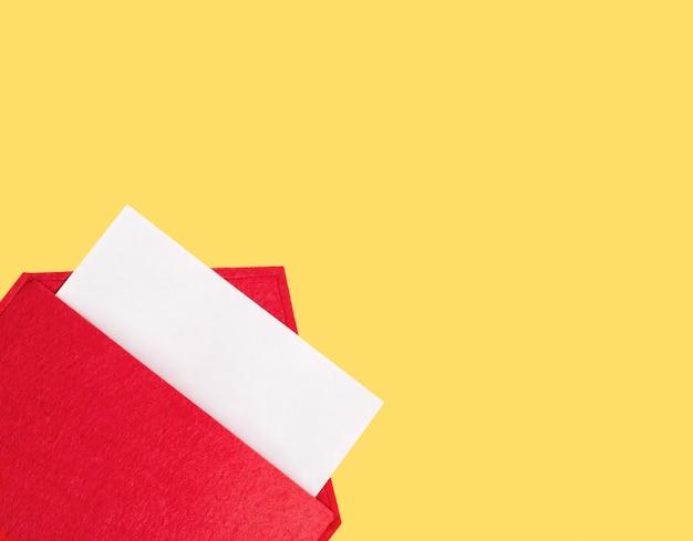Czerwona otwarta koperta z kartką papieru makiety na żółtym tle