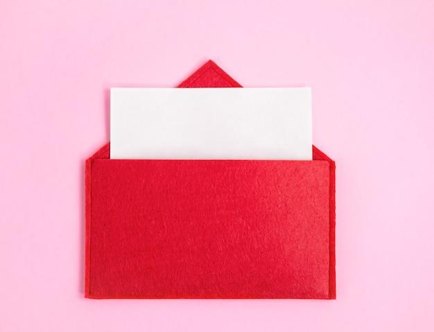 Czerwona otwarta koperta z kartką papieru z makiety na różowym tle z copyspace. walentynki koncepcja wakacje i notatki miłosne