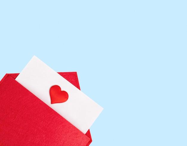 Czerwona otwarta koperta z kartką papieru z sercem na niebieskim tle