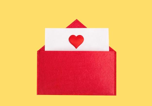 Czerwona otwarta koperta z kartką papieru z sercem na żółtym tle z copyspace. walentynki koncepcja wakacje i notatki miłosne