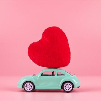 Czerwona ozdoba kształt serca na zabawki mini samochodu z miejsca kopiowania tekstu na różowo. miłość, ślub, romantyczne i szczęśliwe walentynki wakacje koncepcja