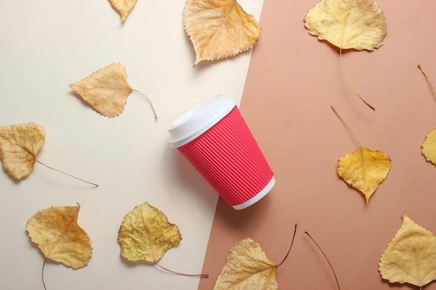 Czerwona papierowa filiżanka kawy i opadłe żółte liście na beżowym brązowym stole. widok z góry