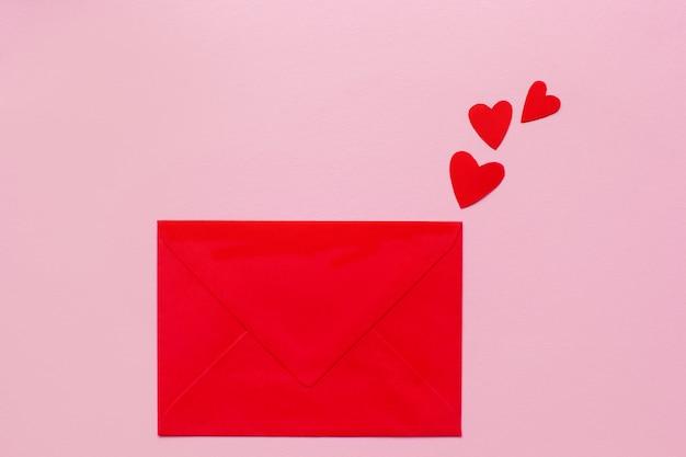 Czerwona papierowa koperta i małe czerwone serca kłama na różowym tle