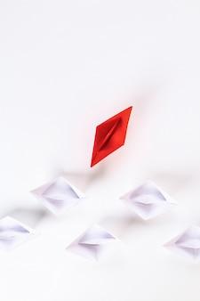 Czerwona papierowa łódź wśród innego bielu.