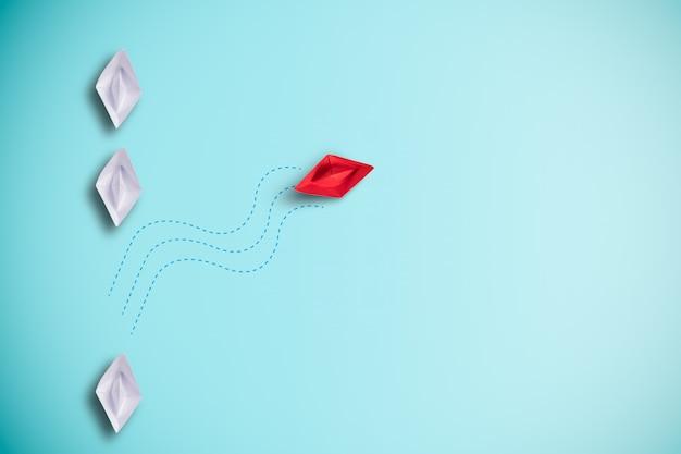 Czerwona papierowa łódź żegluje z białego papieru łódkowatego wirtualnego morza. zakłócenie nowych normalnych odkryć nowego biznesu i innej koncepcji myślenia.