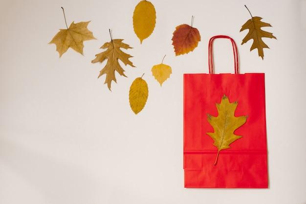Czerwona papierowa torba na zakupy z jesiennych liści