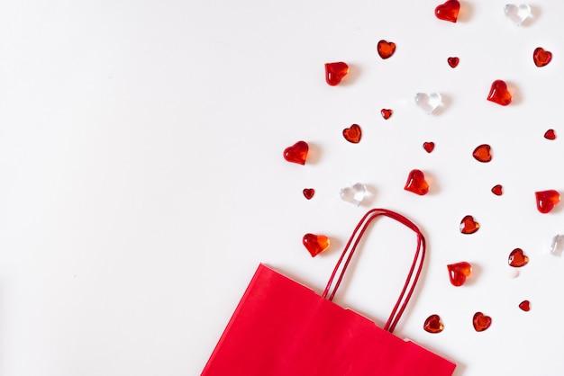 Czerwona papierowa torba z sercami obok. szablon karty z pozdrowieniami z miejsca kopiowania, projektowania tekstu, blogi w mediach społecznościowych.