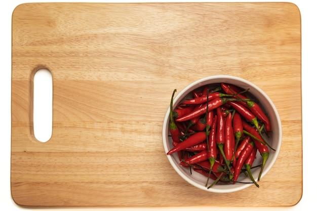 Czerwona papryczka chili w misce na drewnianej desce do krojenia