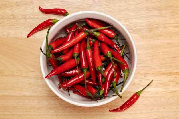 Czerwona papryczka chili w misce na drewnianej powierzchni