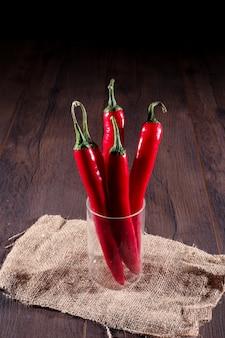 Czerwona papryczka chili w szkle na worze na drewnianej powierzchni
