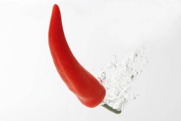 Czerwona papryczka chili wchodząca w wodę