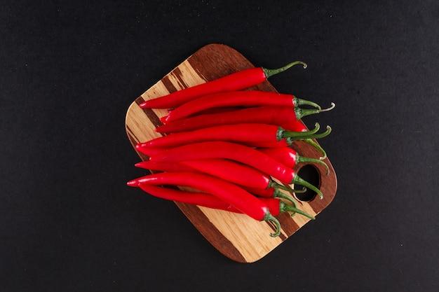 Czerwona papryka chili na widok z góry deska do krojenia drewniana na czarnej powierzchni
