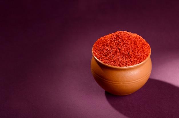 Czerwona papryka chili w proszku w glinianym garnku