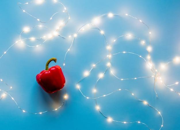 Czerwona papryka słodka z bajkowymi światłami na niebieskim tle. powyżej widok