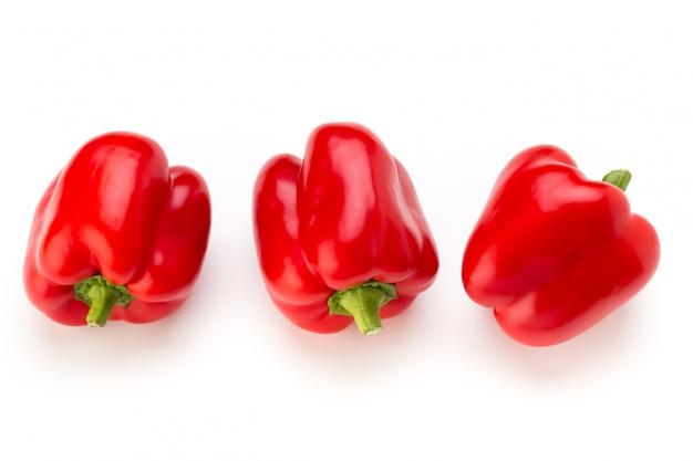 Czerwona papryka z pół i liśćmi na białym tle.