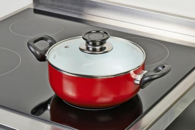 Czerwona patelnia ceramiczna z pokrywą na płycie elektrycznej