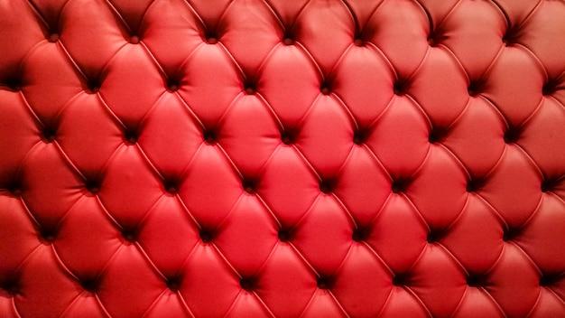 Czerwona pikowana sofa tło