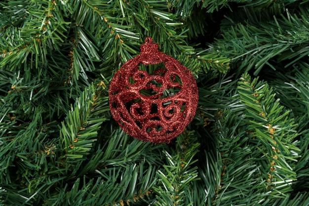 Czerwona piłka boże narodzenie na białym tle na gałęzi choinki.