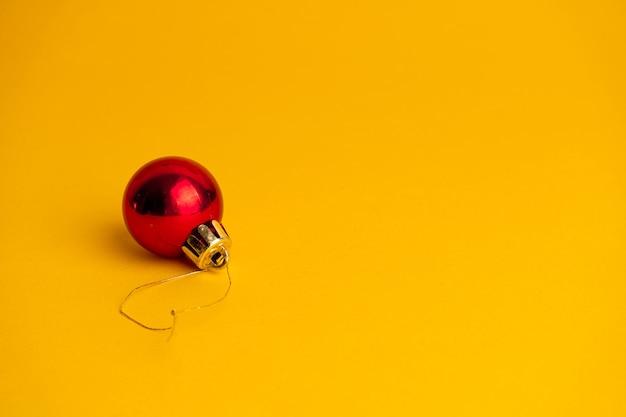 Czerwona piłka ozdoba choinki na żółto