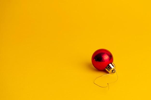 Czerwona piłka ozdoba choinki na żółtym tle.