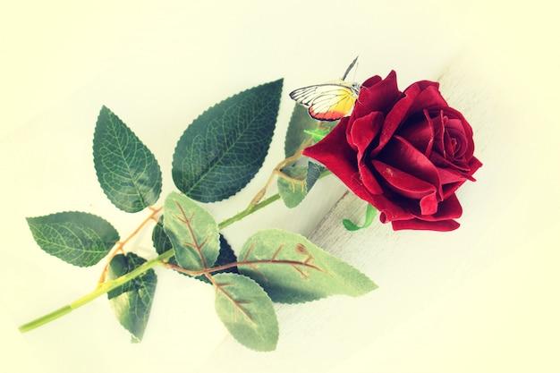 Czerwona plastikowa róża na bielu.
