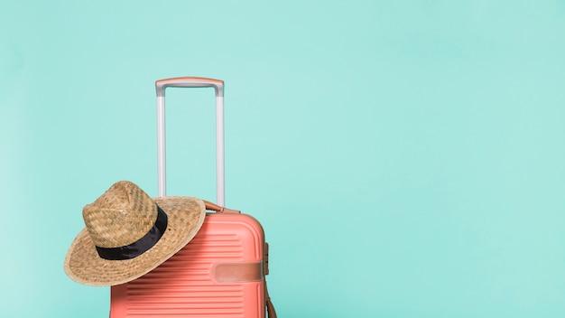 Czerwona plastikowa walizka z kapeluszem