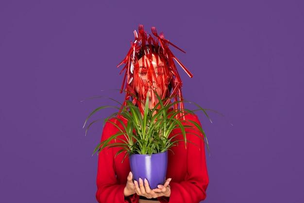 Czerwona plastikowa zastawa stołowa na kobiecie trzymającej roślinę