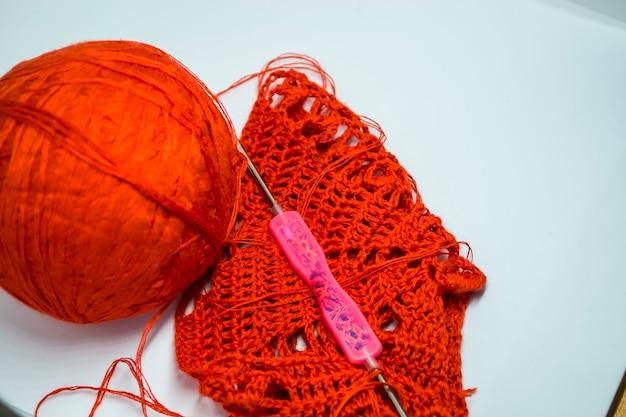 Czerwona plątanina nici dziewiarskich na drutach