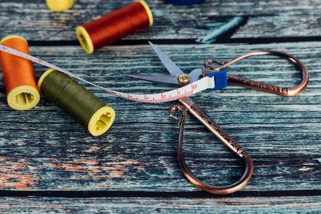 Czerwona, pomarańczowa i zielona szpulka nici. nożyczki i krawcowa miara na drewnianym tle.