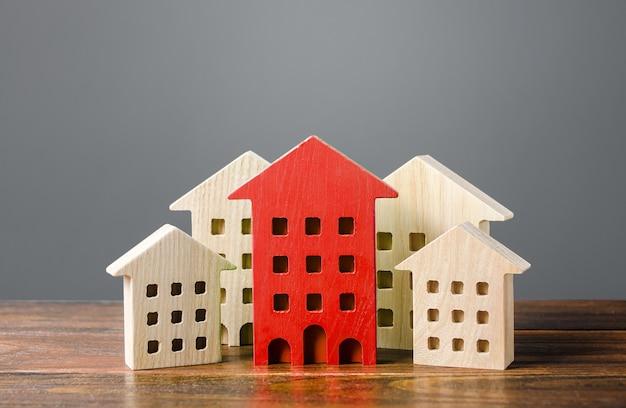 Czerwona postać budynku mieszkalnego wyróżnia się spośród reszty domów.