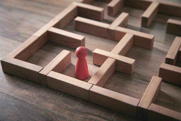 Czerwona postać ludzka stojąca w labiryncie.