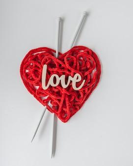 Czerwona przędza dziewiarska z igłami i drewnianym napisem love