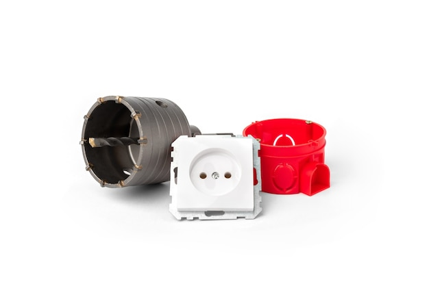 Czerwona puszka elektryczna do gniazd, gniazda i korony diamentowej na białym tle.