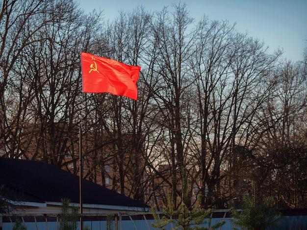 Czerwona radziecka flaga jasno świeci w słońcu na przedmieściach za płotem